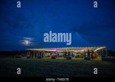 Group of People at Outdoor Dinner Party Under Large Tent at Dusk - Stock Photo