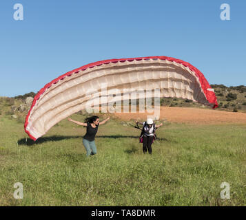 Female flight instructor, teaching a woman to take off with a paraglider in the field on a sunny day of blue sky - Stock Photo