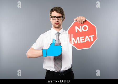 serious businessman in glasses with paper cut thumb up holding red card with no meat lettering on grey background - Stock Photo