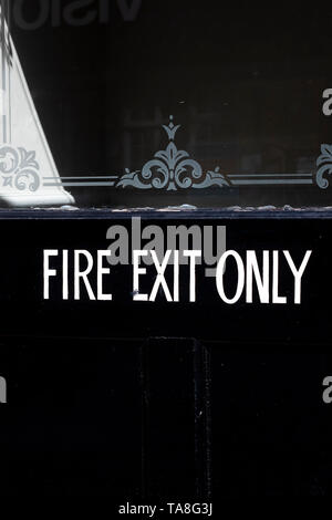 emergency fire exit only sign on black painted timber door to retail premises - Stock Photo