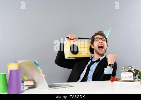 happy businessman sitting at workplace in party cap with vintage tape recorder and rejoicing on grey background - Stock Photo