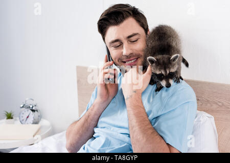 smiling handsome man talking on smartphone while funny raccoon sitting on his shoulder - Stock Photo