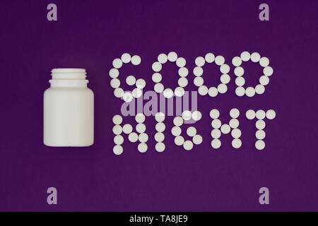 Inscription Good night made from white pills. Pill bottle on violet background. Insomnia concept - Stock Photo