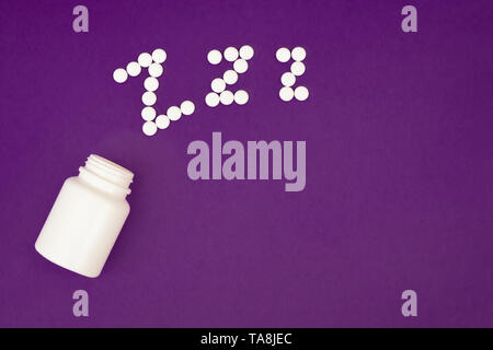 Inscription zzz made from white pills spilling from pill bottle on violet background - Stock Photo