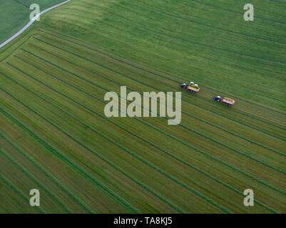 Drone shot of tractors working on agriculture field - Stock Photo
