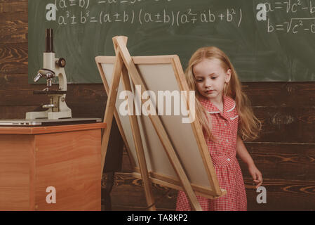 Cute girl artist painting picture on canvas on easel. Little child learn drawing on studio easel, vintage filter - Stock Photo