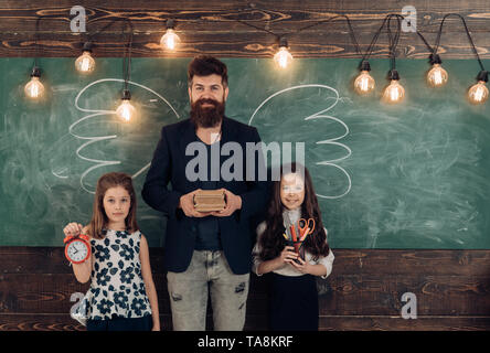 Teacher and girls pupils in classroom, chalkboard on background. Children and teacher with drawn by chalk wings. Man with beard and schoolgirls with - Stock Photo