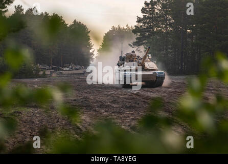 Soldiers aboard M1A2 Abram Tanks from 1st Squadron, 4th Cavalry Regiment, 1st Armored Brigade Combat Team, 1st Infantry Division start to move out, as part of an Initial Ready Task Force (IRTF) exercise, at Johanna Range, Poland, May 20, 2019. An IRTF is similar to an Emergency Deployment Readiness Exercise (EDRE) but on a smaller scale. An IRTF is a no-notice, rapid-deployment exercise designed to test a unit's ability to alert, marshal, and deploy forces and equipment for contingency operations or an emergency disaster. (U.S. Army photo by Sgt. Thomas Mort) - Stock Photo