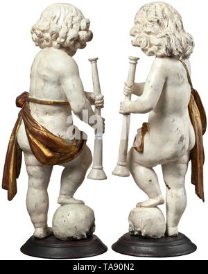 A pair of German or Flemish cherubs, circa 1700 Three-dimensional carved figures of lime wood with old paint in white and gold. Depiction of boys in loincloths, each holding a flute and with a foot resting on a skull. On a round plinth (supplemented?). Height of each 50 cm. historic, historical, fine arts, art, 18th century, Additional-Rights-Clearance-Info-Not-Available - Stock Photo