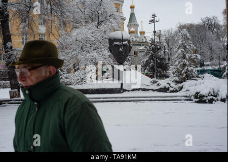 An Old Bulgarian man walks past the Stefan Stambolov Monument, in the snow of Crystal Park, Sofia, Bulgaria, Europe - Stock Photo