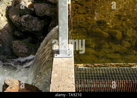 Spillway over a small dam close up. Water level difference. Regulation of the water level in the lake.