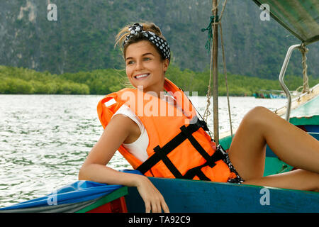 Young woman enjoy her ride on long-tail boat to the green islands during vacations in Thailand - Stock Photo