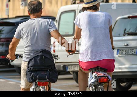 GARDA, LAKE GARDA, ITALY - SEPTEMBER 2018: Two people riding bikes and holding hands in Garda on Lake Garda - Stock Photo