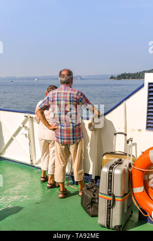 GARDA, LAKE GARDA, ITALY - SEPTEMBER 2018: Two people with luggage standing on the deck of a passenger ferry on a journey across Lake Garda. - Stock Photo