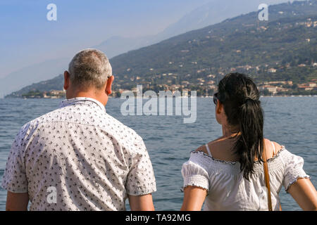 GARDA, LAKE GARDA, ITALY - SEPTEMBER 2018: Two people standing on a  passenger ferry on a journey across Lake Garda looking out at the scenery. - Stock Photo