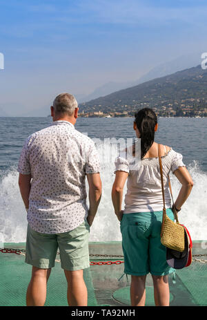 GARDA, LAKE GARDA, ITALY - SEPTEMBER 2018: Two people standing on the front of a  passenger ferry on a journey across Lake Garda with waves and spray. - Stock Photo