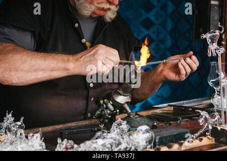 A glassblower makes a glass product. Handwork. Profession or occupation or hobby. - Stock Photo