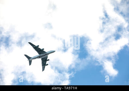 Qatar Airbus airplane flies over the city, blue and cloudy sky. Qatar Airways is the national airline of Qatar, based in Doha - Stock Photo