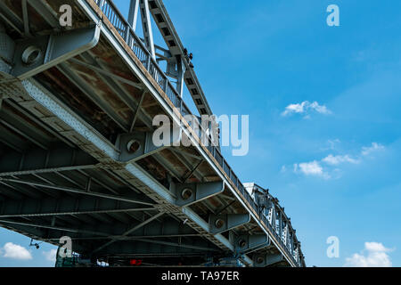 Steel bridge structure against blue sky and white clouds. Iron bridge engineering construction. Strong and strength metal bridge. Road bridge - Stock Photo