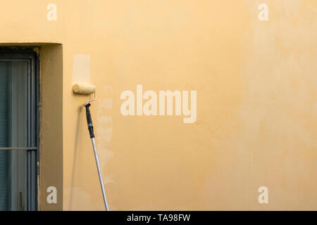 Painter paints building exterior wall with a roller. Roller with long stick manually painting building with yellow paint