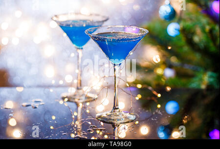 Christmas image of two wine glasses with blue cocktail and garland - Stock Photo