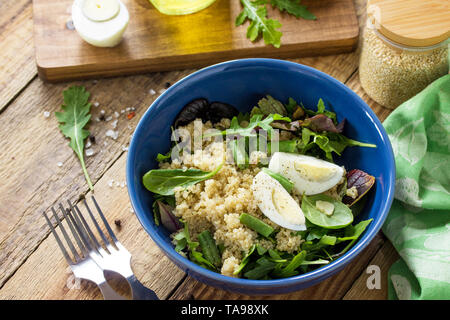 Diet menu, Vegan food. Healthy salad with quinoa, green beans, eggs and salad dressing on rustic table. - Stock Photo