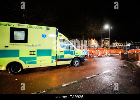 London, United Kingdom - Mar 5, 2017: Yellow NHS ambulance driving fast on the repaired with roadworks street in central london at night  - Stock Photo