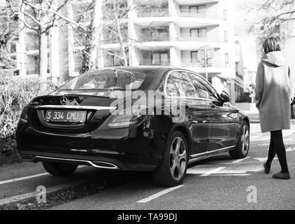Strasbourg, France - Feb 23, 2017: Woman walking toward new status Mercedes-Benz E220d diesel car parked on a calm street in French city - Stock Photo