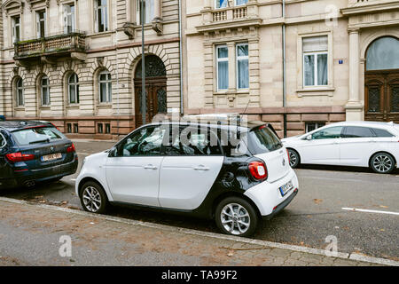 Strasbourg, France - Dec 27, 2017: Parked in the street white Mercedes Smart car - french apartment buildings in the background - Stock Photo