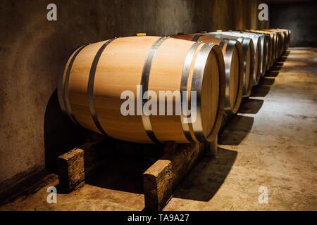 Wine maturing in oak barrels in a cellar. - Stock Photo