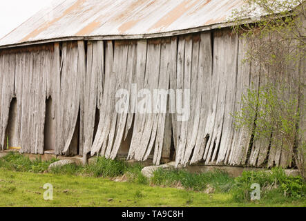 Old weathered barn with lifting boards and sloping roof - Stock Photo