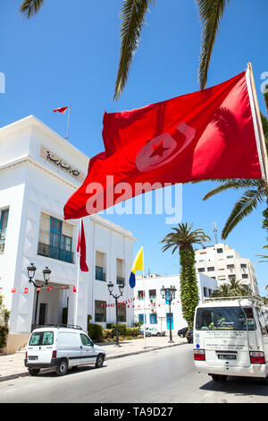 SOUSSE, TUNISIA, AFRICA-CIRCA MAY, 2012: Tunisian national flag waves against administrative building in Sousse city. All government buildings must ha - Stock Photo