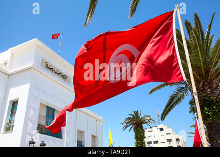 Red Tunisian national flag waves against administrative building in Sousse city. All government buildings must have flags on facade. Tunisia, the Afri - Stock Photo
