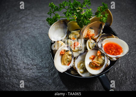 enamel venus shell cooking pan seafood plate with Shellfish Clams ocean gourmet dinner cooked with herbs and spices chilli sauce seafood on dark backg - Stock Photo