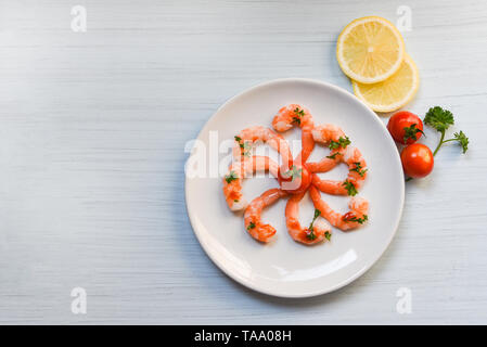 Seafood plate with shrimps prawns ocean gourmet dinner served on plate seafood cooked with ketchup herbs and spices on white wooden background - Stock Photo