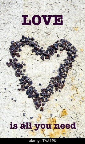 A red stone pebble heart on the dry desert ground with inspirational text. - Stock Photo