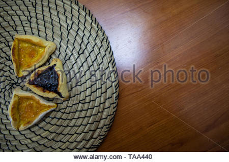 Hamantash Purim blueberry and apricot jam cookies with wooden table background - Stock Photo