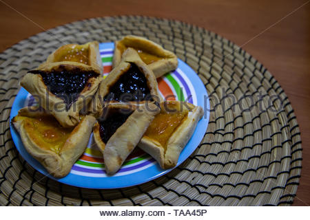 Hamantash Purim blueberry and apricot jam cookies in colored plate with wooden table background - Stock Photo