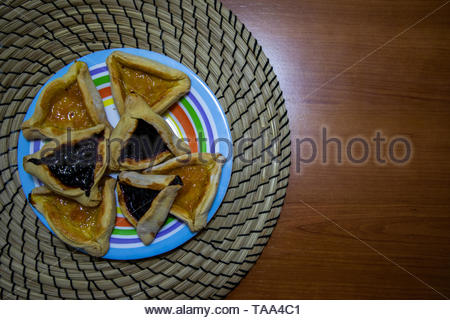 Hamantash Purim blueberry and apricot jam cookies on colored plate with wooden table background - Stock Photo