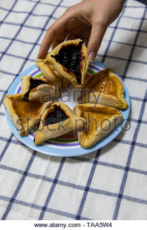 woman hand holding Hamantash Purim Blueberry and apricot jam cookies on colored plate on blue and white tablecloth - Stock Photo