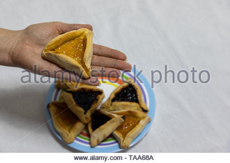 Woman hand holding hamantash cookie on top of colorful plate with more hamantash cookies - Stock Photo