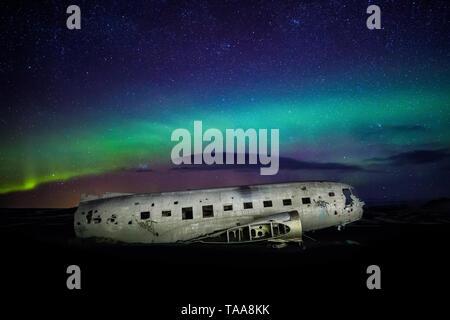 The crashed DC-3 Plane wreck with Northern Lights & Aurora Borealis at Solheimasandur, Iceland - Stock Photo
