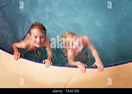 Two happy little kids who are brothers are smiling as they swim in their family backyard swimming pool on a summer day. - Stock Photo
