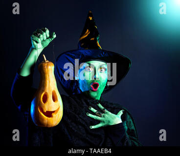 Witch with green skin holding carved Halloween pumpkin lantern at dark background - Stock Photo