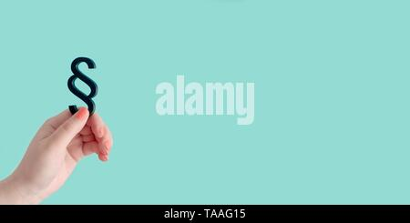 Woman hand hold a paragraph symbol of Law and Justice in front of blue background. Panoramic image with copy space. - Stock Photo