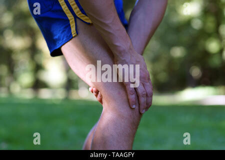 Knee injury after jogging workout in the park. Man stopped running and holds his hand on his knee. Morning Shot with Sunlight and warm effect. - Stock Photo
