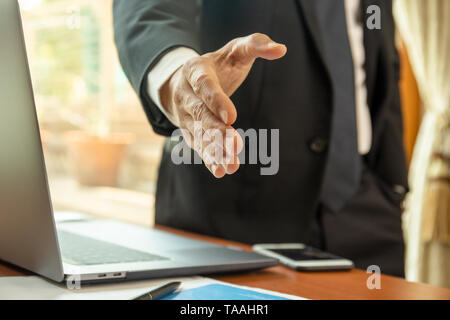 Businessman standing and reaching out hand for shaking. - Stock Photo