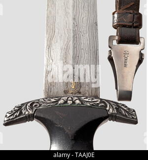 An SS honour dagger with Damascus blade, Eickhorn, Solingen Damascus blade with high-etched, gilded motto 'Meine Ehre heißt Treue' between oak leaf branches. On reverse side high-etched maker's logo. Silver grip mountings with oak leaf décor in relief, black wooden grip with nickel-silver national eagle and enamelled SS emblem. Steel scabbard with original, black leather cover (minimal abrasions) and silver-plated scabbard mountings. Short black leather hanger with belt loop for attaching to coat. Length 37 cm. Extremely rare, only light signs of usage and age. historic, hi, Editorial-Use-Only - Stock Photo