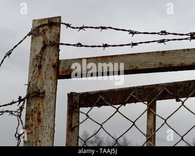 Old and rusty security fence and door with barbed wire on top - Stock Photo