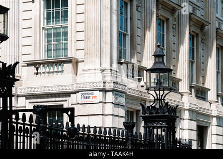London, UK - May 14, 2019:  Street names signs Downing Street and Whitehall in the gate of 10 Downing Street, the residence of Prime Minister of the U - Stock Photo